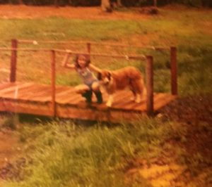 """Alice and her dog, Buffy, circa 1970 something.  """"The Woods"""" are in the background."""